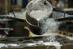 Detail of metal casting, pouring molten aluminum silver colored liquid into a mold creating smoke in a industrial environment, workshop space