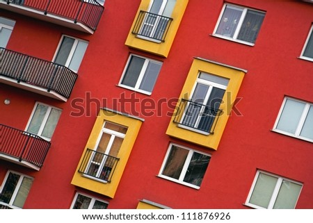 Detail of modern apartments with balconies and red walls