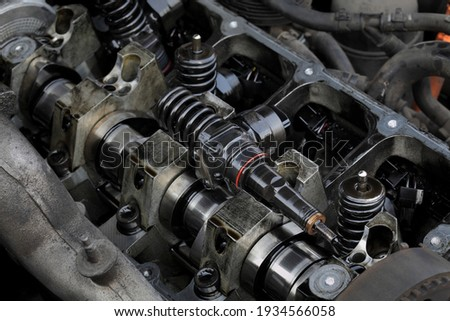 Detail of modern diesel engine repair, closeup of injectors in cylinder head with camshaft