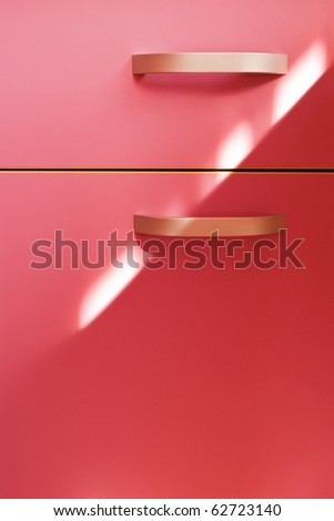 detail of modern handle on pink furniture