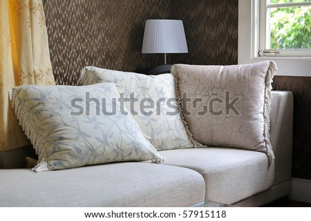 Detail of modern living room with table lamp and pillow cushions on sofa
