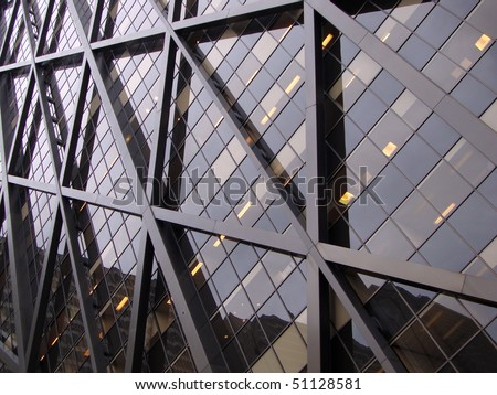 Detail of Modern Office building in downtown San Francisco with another building reflected in its windows and some lights on.  Good for patterns and backgrounds.