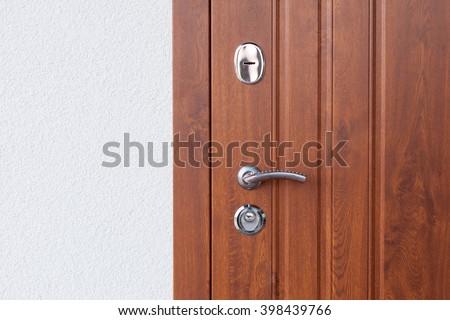 Detail of Modern style metallic door handle on wooden door #398439766