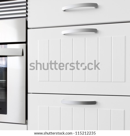 Detail of modern white kitchen. Drawers and oven.