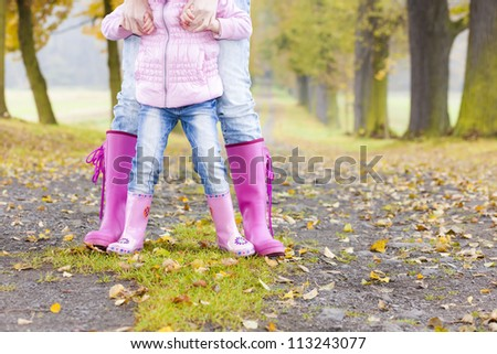 detail of mother and daughter wearing rubber boots in autumnal alley