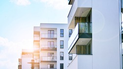 Detail of new luxury house and home complex. Glass surface with sunlight. Rising sun on the horizon. Part of modern residential apartment with flat building exterior.  Velvia graphic filter.