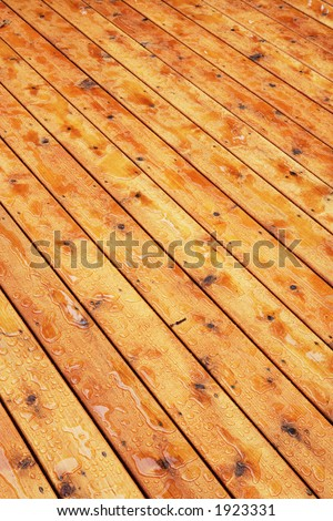 Detail of newly sealed wood deck with water.