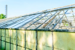 Detail of old abandoned greenhouse with lots of broken glass windows.