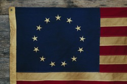 Detail of old dingy Betsy Ross Flag designed during the American Revolutionary War features 13 stars to represent the original 13 colonies.