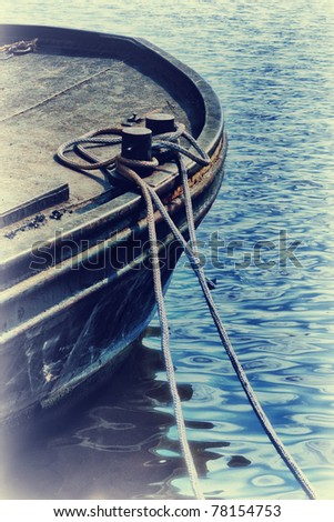 Detail of old fishing boat tied with rope at seacoast