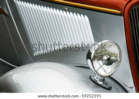 Detail of old silver collectible car,cool light reflections.