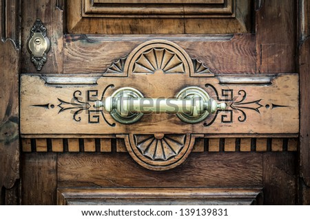Detail of old wooden door with horizontal metal handle on board with carved pattern and keyhole over it. Dark brown solid front door in vintage and antique style. Exterior and facade.