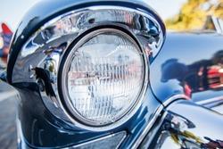 Detail of oldtimer vintage car. Front light of retro classic automobile.