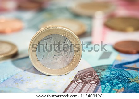 Detail of one euro coin, other euro coins and notes in background
