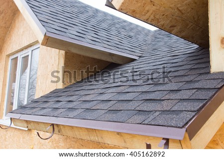 Detail of overlapping roofing tiles on a new build wooden house with dormer windows #405162892