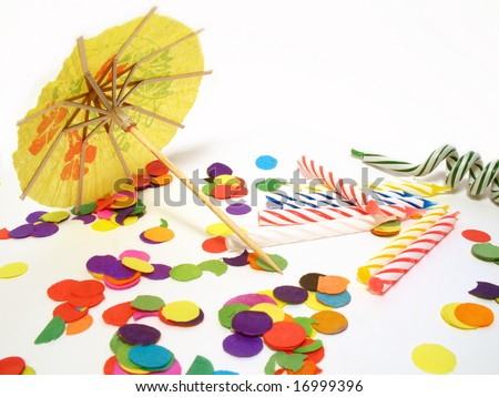 Detail of party still life, confetti, candles and umbrella