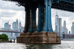 Detail of Pillar of Manhattan Bridge against cityscape of New York City. Steel Abutment With Bolt and Rivet Connections. Engineering and architecture