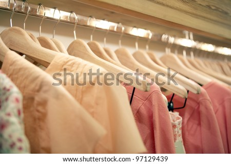 Detail of pink clothes hanging on wooden hangers in a fashion store.