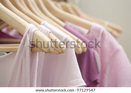 Detail of pink clothes hanging on wooden hangers in a fashion store. - stock photo
