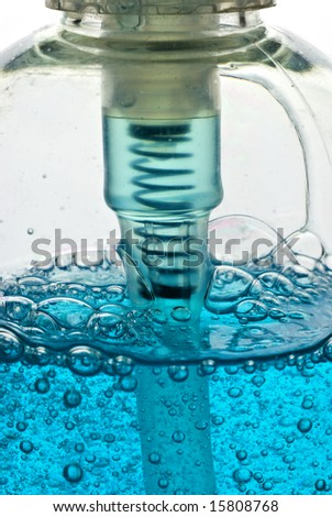 detail of plastic pump bottle filled with bubbly, clear blue product