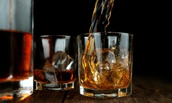 Detail of pouring whiskey into glass on black background