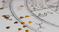 Detail of printed natal chart with astrology moon and heart shaped golden sequins
