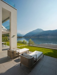 Detail of private terrace overlooking Lake Ceresio in Switzerland. Two deck chairs in the foreground. it's a sunny day and it's midsummer