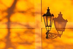 Detail of retro street light on the wall at sunset. Prague, Czech Republic