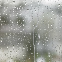 detail of roll off raindrops on window glass