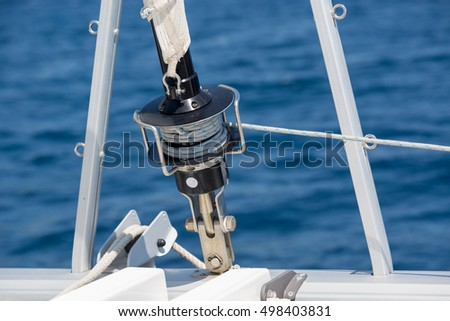 Detail of rolled sail of the mainstay of a sailboat. Background of mountains and sea. Dalmatian sea, Croatia.