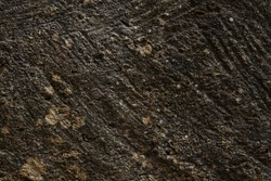 Detail of rough and porous dark sandstone wall texture