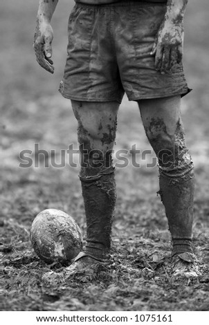 Detail of rugby player, ball and mud.