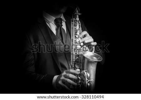 Detail of Saxophone and man hands isolated against black background. Close up studio portrait, black and white image.
