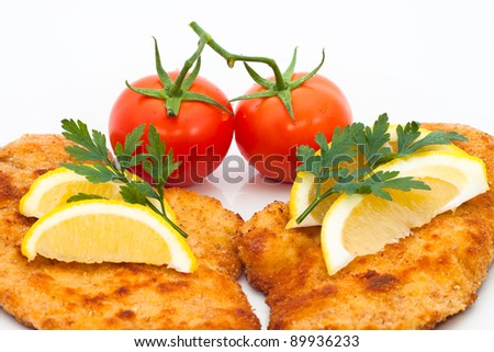 Detail of schnitzel with lemons and tomatoes, isolated on white background.