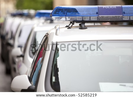 Detail of several police cars in a row, shallow deep of field.