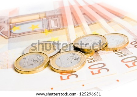 detail of some euro coins on 50-euro banknotes on white background