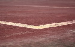 detail of some white and yellow lines painted on a brown sport court