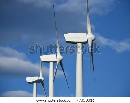 Detail of some wind turbines with clouds - stock photo