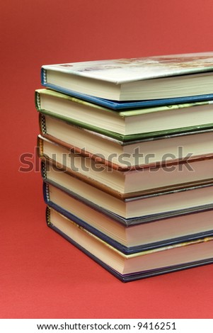 detail of 7 stack books on red background