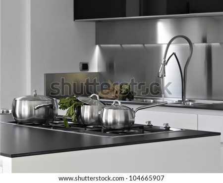detail of steel saucepans with parsley in a modern kitchen