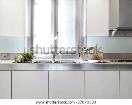detail of steel sink under the window in a modern white kitchen