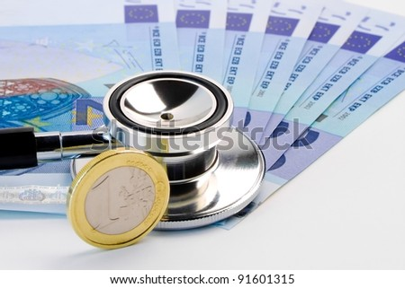 detail of stethoscope on banknote near euro coin on white background