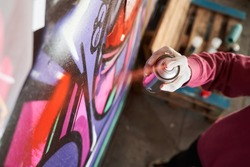 Detail of street artist painting colorful graffiti on public wall. Modern art concept with urban guy drawing live murales with multi color aerosol spray. Focus on the boy hand with spray paint can