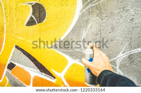 Detail of street artist painting colorful graffiti on public wall - Modern art concept with urban guy drawing live murales with multi color aerosol spray - Vintage filter with focus on yellow paint