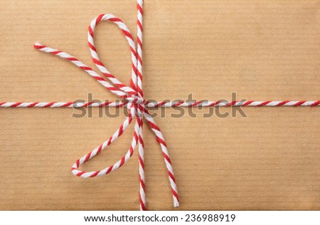 detail of string and brown paper parcel:red and white striped  string bow against brown wrapping paper