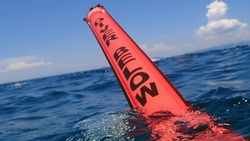 Detail of surface marker buoy Diver Below. Diving buoy SMB on the surface of the blue ocean and blue sky with sunshine. Deployable buoy on the surface, diver calling boat. Safe diving practice.