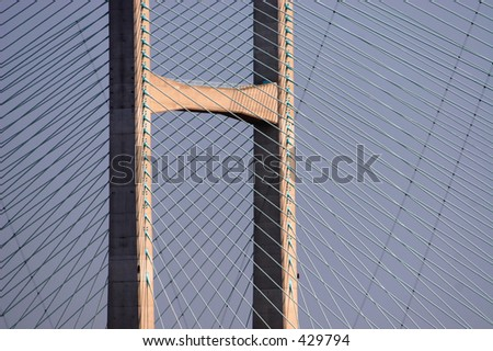 Detail of suspension bridge superstructure, illustrating latticework pattern of cables, photographed in evening sunlight.