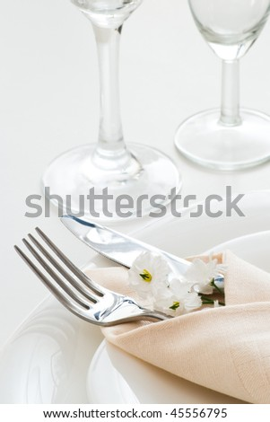 detail of table setting with white little flower - stock photo