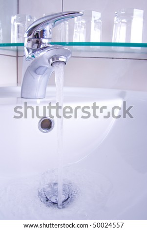 Detail of tap with running water and glasses in background.