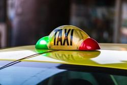 Detail of taxi sign on yellow taxi car in Bucharest, Romania